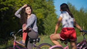 Två unga cyklister meddelar och skrattar på en cykla tur i parkera, på en solig sommardag arkivfoton