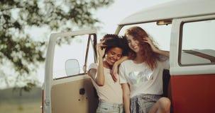 Två unga damer med lockigt hår som beside sitter av den orange bussen för tappning och att le se de stock video