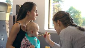 Två unga damer som matar en behandla som ett barn på drevet Fotografering för Bildbyråer