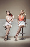 Två unga damtoalett som tar omsorg av deras hår royaltyfria foton