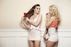 Två unga skönhetdanandeförberedelser till ett parti Arkivbild