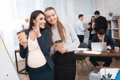 Två unga flickor fördelar skvaller på kaffeavbrott Skvaller i kontoret arkivfoto