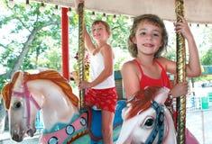 Två unga flickor på karusell arkivbild