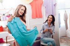 Två unga flickor på shopping Flickor väljer kläder i lagret Flickor i visningslokalen Arkivfoto