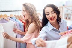 Två unga flickor på shopping Flickor väljer kläder i lagret Flickor i visningslokalen Royaltyfri Fotografi