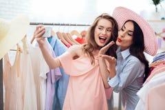 Två unga flickor på shopping Flickor väljer kläder i lagret Flickor i visningslokalen Royaltyfria Foton