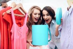 Två unga flickor på shopping Flickor väljer kläder i lagret Flickor i visningslokalen Royaltyfria Bilder
