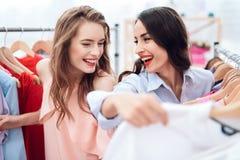 Två unga flickor på shopping Flickor väljer kläder i lagret Flickor i visningslokalen Fotografering för Bildbyråer
