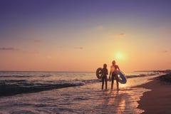 Två unga flickor promenerar havsstranden på solnedgången bak dem Sommarsemester på havet Ett företag av tonåringar badar i havet Arkivfoton