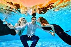 Två unga flickor som är förälskade, en blondin och en brunett, bad i klänningar och lek med en grabb i en vit skjorta under vatte arkivbild