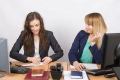 Två unga flickor som arbetar i ett kontor och att göra ett pappers- flygplan och andra med hatblickar på henne Royaltyfri Foto