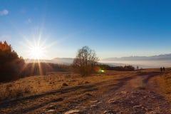 Två unga flickor som går genom hela solnedgången Arkivfoton