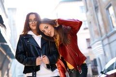 Två unga flickor som går staden som har gyckel arkivfoton