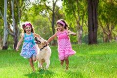 Två unga flickor som kör med en golden retriever på gräset royaltyfria bilder