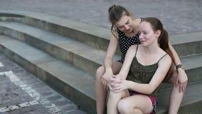 Två unga flickor som sitter på stenmomenten, spenderar tidsamtal stock video