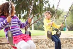 Två unga flickor som spelar på gunga i lekplats Royaltyfria Foton