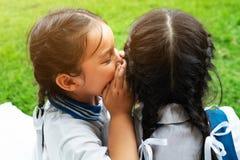 Två unga flickor som viskar och delar en hemlighet under lekplatsperiod på bakgrund för grönt exponeringsglas arkivbild