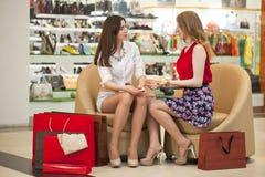 Två unga flickvänner som sitter i shoppa och, kopplar av efter shoppi Fotografering för Bildbyråer
