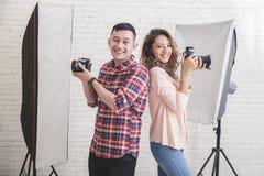 Två unga fotografer tillbaka som drar tillbaka att le, medan se ca Arkivfoto