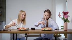 Två unga gladlynta vänkvinnor äter sushi, och temakien i kvällsmål i hem i afton, ler de lager videofilmer