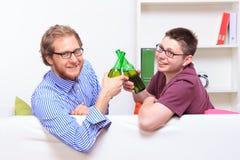 Två unga grabbar med öl på soffan Royaltyfri Bild