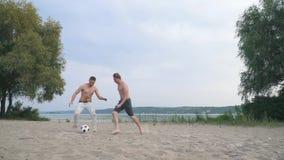 Två unga grabbar som spelar fotbollkonkurrens mellan folkvänner har en gyckel som tillsammans utomhus spenderar aktiv tid stock video