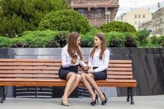 Två unga härliga affärskvinnor som sitter på en bänk arkivbild