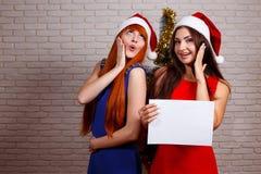 Två unga härliga förvånade chockade kvinnor med det tomma arket av royaltyfria foton