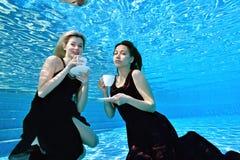 Två unga härliga flickor, blondin och brunett, simmar undervattens- i pölen med vita koppar i deras händer, blick på kameran och arkivfoton