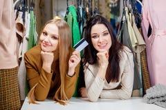 Två unga härliga flickor gör shopping med en kreditkort och att le i ett klädlager Arkivbild