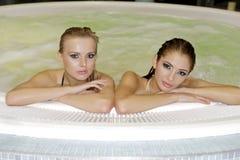 Två unga härliga flickor i bubbelpool Royaltyfri Bild