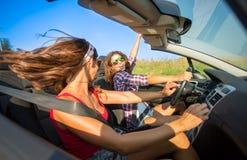 Två unga härliga flickor som kör i en cabriolet, medan dansa royaltyfri fotografi
