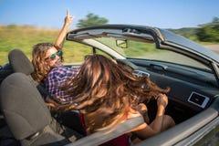 Två unga härliga flickor som kör i en cabriolet, medan dansa royaltyfri foto