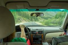 Två unga härliga flickor som reser med bilen i bergen av Altaien, kör förbi den slingrande vägen Kvinnablick in till fotografering för bildbyråer