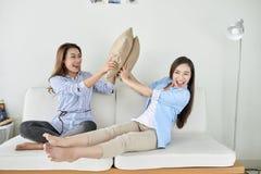 Två unga härliga gladlynta flickvänner som hemma som sitter på soffan skrattar royaltyfria bilder