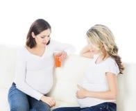Två unga härliga gravida kvinnor på en soffa Royaltyfri Foto