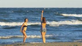 Två unga härliga kvinnor i baddräkten som tar bilder med den smarta telefonen och har gyckel på stranden arkivfilmer