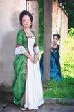 Två unga härliga kvinnor i långa medeltida klänningar Royaltyfri Bild