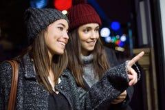 Två unga härliga kvinnor som ser shoppafönstret på natten arkivbilder