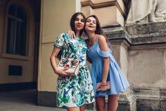 Två unga härliga kvinnor som utomhus kramar Flickor som har gyckel i stad Bästa vän hänger ut arkivbilder