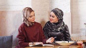 Två unga härliga muslimska affärskvinnor i hijab som arbetar med dokument i kafé lager videofilmer