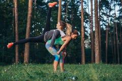 Två unga idrottskvinnor som tillsammans gör partnergenomkörare i skog arkivfoton