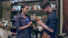 Två unga keramiker som diskuterar den handgjorda giraffstatyetten lager videofilmer