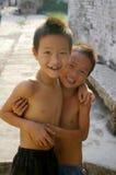 Två unga kinesiska pojkar som ler i en by Arkivbild