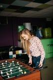 Två unga kontorspersoner som tycker om tabellfotbollleken under deras fria Tid på arbetsplatsen Royaltyfri Bild