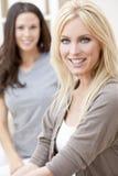 Två unga kvinnavänner hemma på sofaen Royaltyfri Fotografi