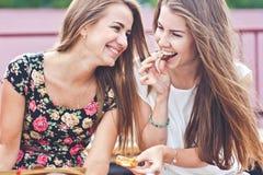 Två unga kvinnlig talar och skrattar, medan äta utomhus- choklader Arkivbild