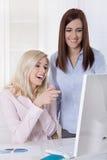 Två unga kvinnliga deltagare i utbildning under mellantiden som ser datummärkning, port Arkivfoto
