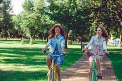 Två unga kvinnliga vänner som rider deras cyklar i parkera royaltyfri foto