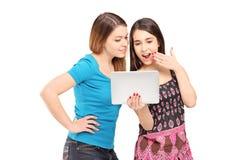 Två unga kvinnliga vänner som tätt tillsammans står och ser Arkivfoton